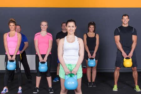 crossfit: crossfit fitness group of people holding kettlebells