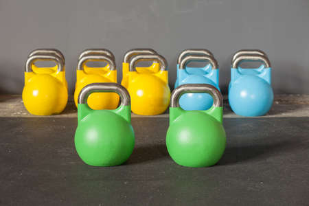 kettle bell: colorful kettlebells in a row in a gym - focus on the front kettle bell Stock Photo