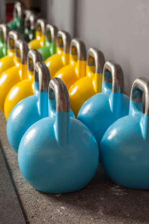 gym dress: colorful kettlebells in a row in a gym Stock Photo