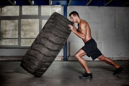 workout: crossfit training - man flipping tire