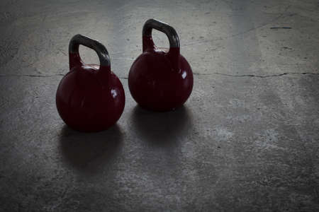 two red kettlebells on a stone floor in a gym - background lighting