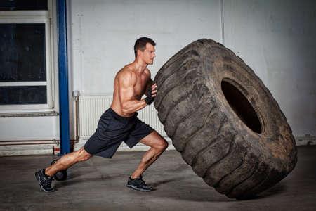 muscular man: crossfit training - man flipping tire
