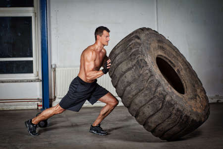crossfit training - man flipping tire