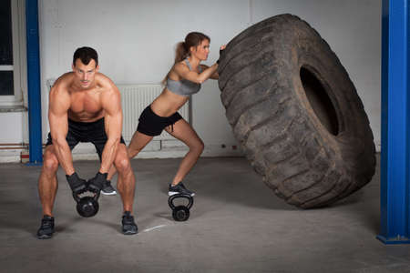 sport training: crossfit training - woman flipping tire Stock Photo
