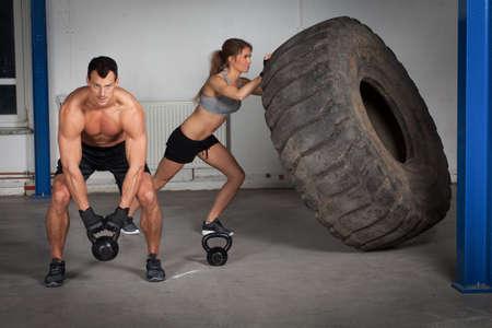 crossfit training - woman flipping tire Stock Photo