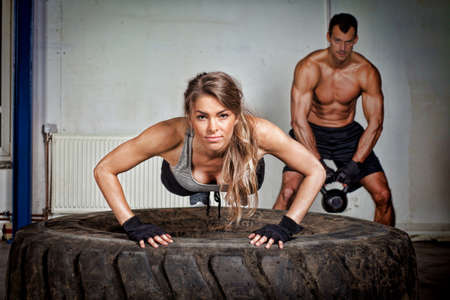 fit woman: Push up on a tire crossfit training