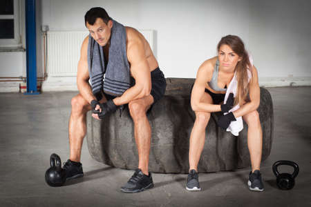 crossfit: woman sitting on tire and relaxing after crossfit fitness training