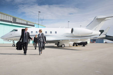 luxury lifestyle: executive business team leaving corporate jet