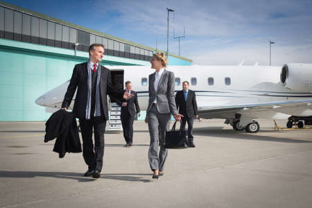 airport business: executive business team leaving corporate jet