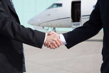 private jet: Businessmen shake hands in front of a corporate jet