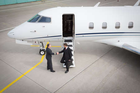 private plane: executive manager leaving corporate jet handshake with pilot
