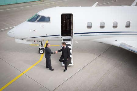 piloto de avion: gerente ejecutivo dejando apretón de manos avión de la empresa con el piloto