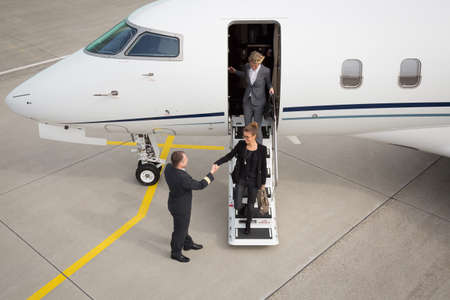 A executive business woman leaving a plane handshake with pilot