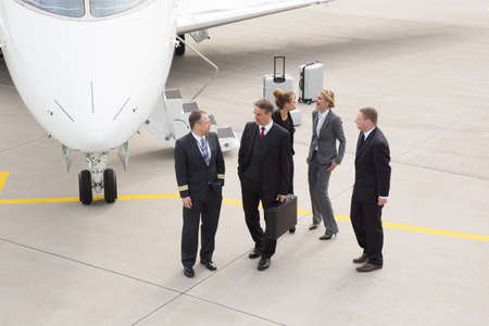 executive business team in front of corporate jet pilot talking to photo