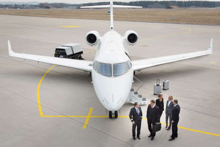 private jet: executive business team in front of corporate jet pilot talking to