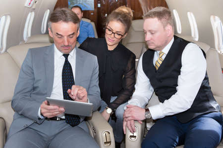 business team traveling in corporate jet and discussing a presentation Фото со стока