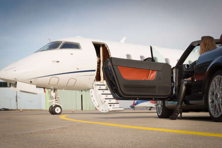 corporate jet: woman convertable car and corporate private jet