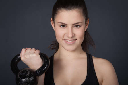 amortization: Woman holding a kettlebell and smiling to camera - crossfit fitness Stock Photo