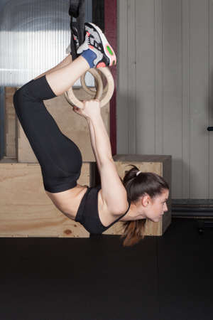 flotation: gymnastics rings - a woman doing crossfit fitness exercise