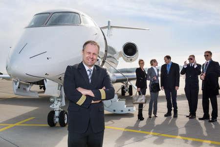 piloto de avion: Piloto de pie delante de jet privado corporativo
