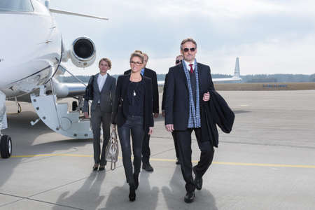 hombre millonario: equipo de negocios ejecutivo dejando avión de la empresa Foto de archivo