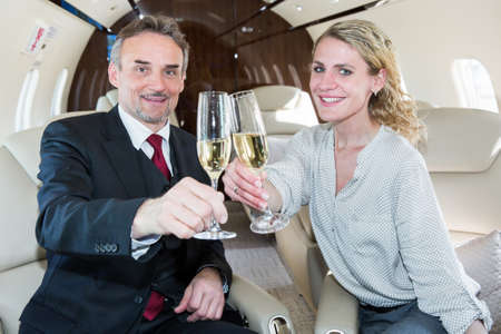 business team traveling in corporate jet and discussing a presentation Stock Photo
