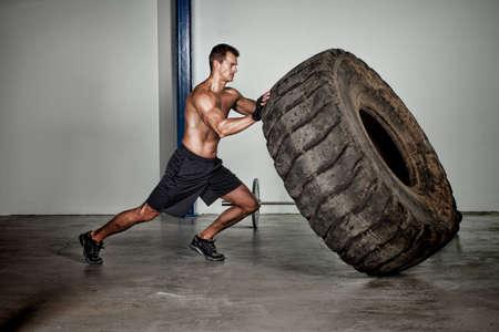 tyres: crossfit training - man flipping tire