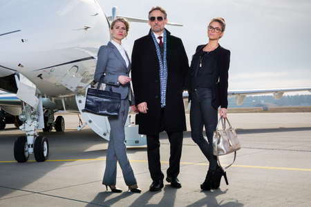 private: business team standing in front of private jet