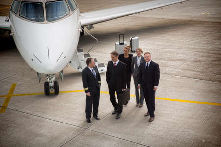 private plane: executive business team in front of corporate jet pilot talking to