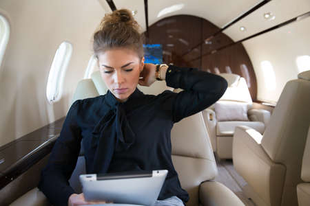 woman in corporate jet looging at tablet computer Фото со стока