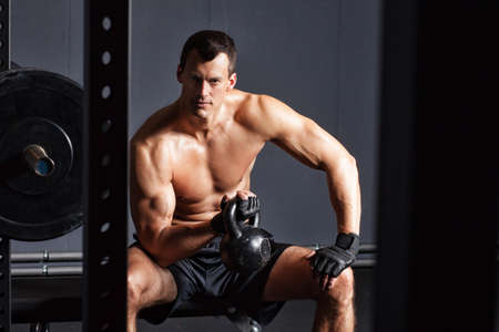 Man sitting and holding a kettlebell - crossfit Stock Photo