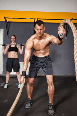 crossfit man swinging rope in a gym Stock Photo