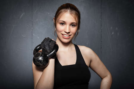 Woman holding a kettlebell and looking to camera - crossfit fitness
