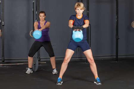 fitness training: vrouw swingende kettlebell - fitnesstraining