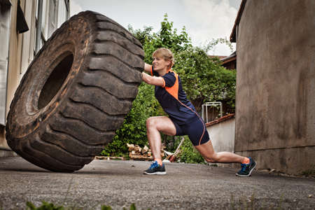 crossfit: woman flipping a tire crossfit training