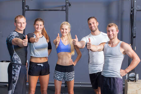 thumbs up - Happy fitness group people showing thumbs gesture Фото со стока