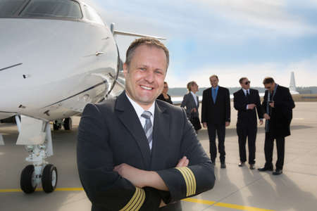 corporate jet: Pilot standing in front of corporate private jet