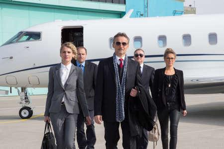 millonario: equipo de negocios ejecutivo dejando avión de la empresa Foto de archivo
