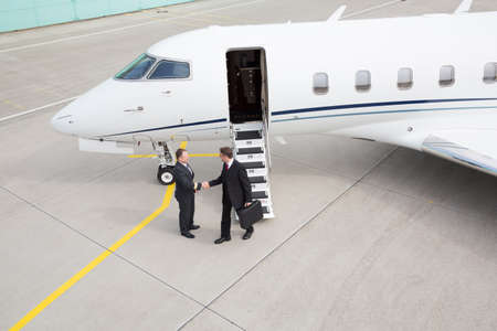business travel: executive manager leaving corporate jet handshake with pilot