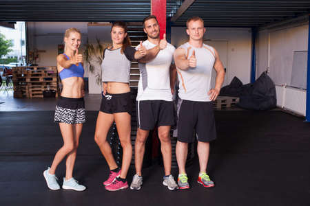 Thumbs up - fitness people showing gesture in gym
