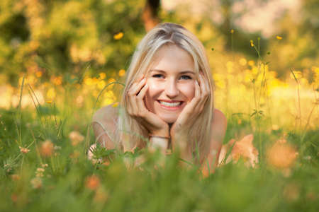 Happy young woman on a summer flower meadow outdoor