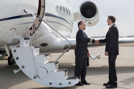 private airplane: executive manager leaving corporate jet handshake with pilot