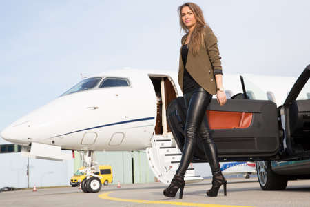 woman convertable car and corporate private jet