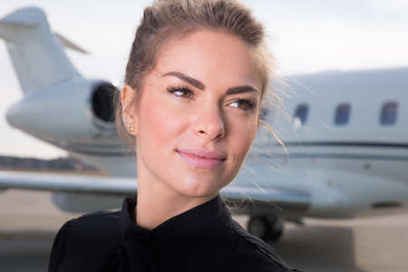 corporate jet: business woman in front of a corporate jet