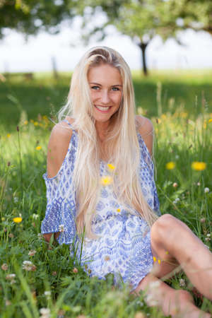young adult woman: Happy girl on a summer flower meadow outdoor Stock Photo