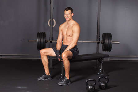 men health: Man sitting at a workout place in a gym and smiling to camera Stock Photo