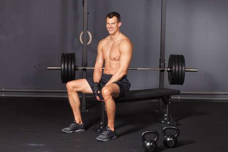 muskeltraining: Man sitzt an einem Training in einem Fitness-Studio und lächelnd zur Kamera