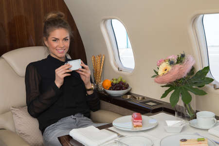 corporate jet: business woman in a corporate jet drinking coffee