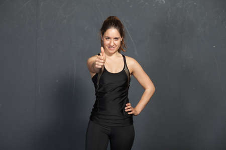 gym dress: Thumbs up - woman in a gym Stock Photo