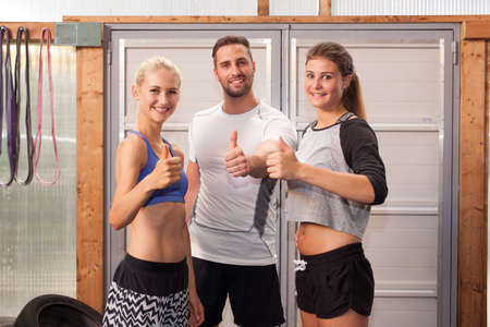 gym dress: Thumbs up - fitness people showing gesture Stock Photo
